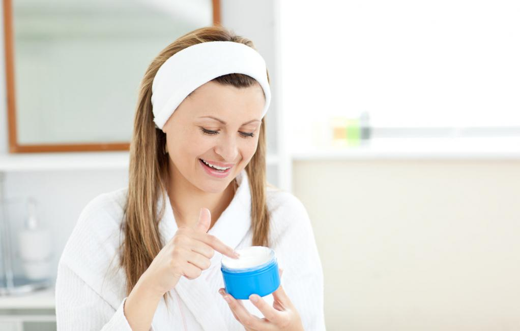 radiant-woman-putting-cream-on-her-face-wearing-a-headband-in-th.jpg